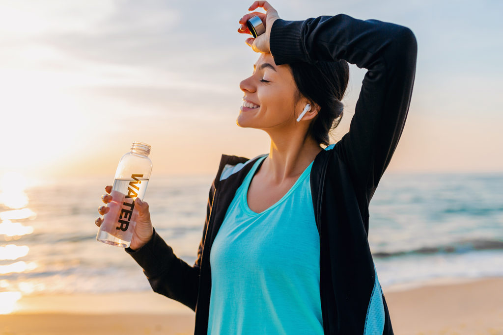 slim woman doing sport exercises on morning sunrise beach in sports wear, thirsty drinking water in bottle, healthy lifestyle, listening to music on wireless earphones,