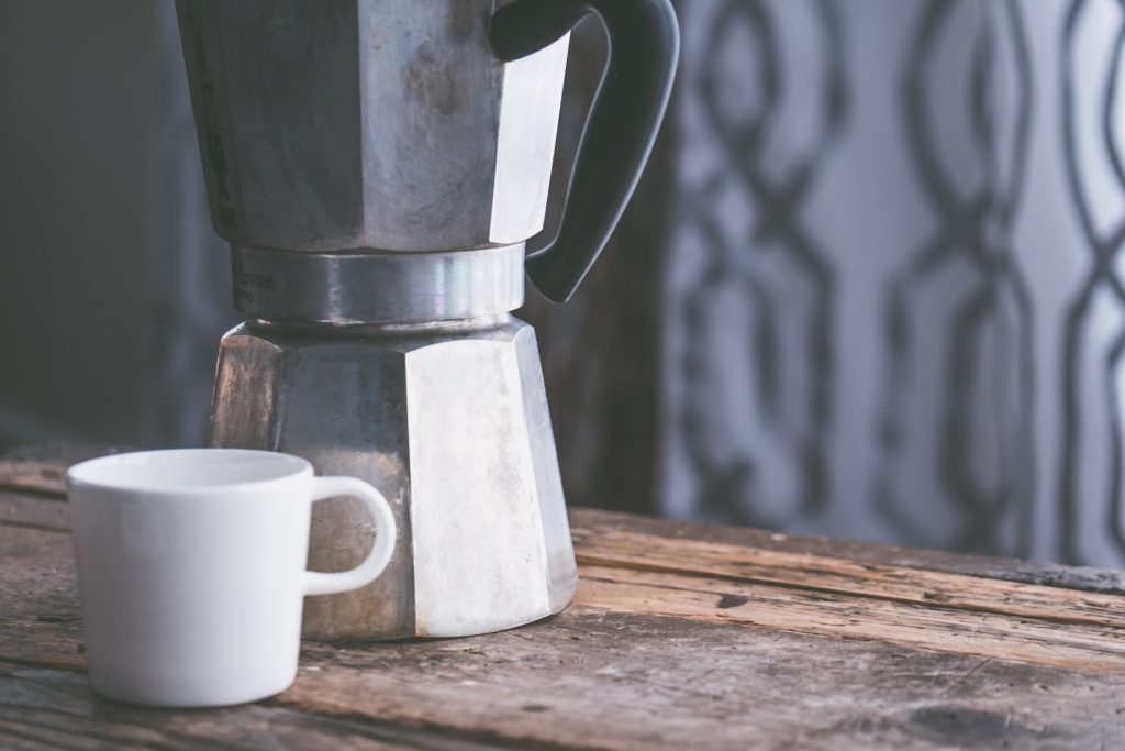 A mug in front of a coffee maker.
