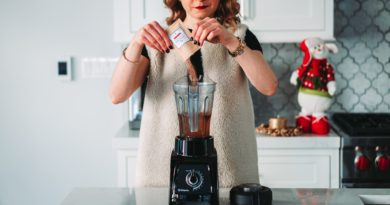 A woman using a blender in a kitchen.